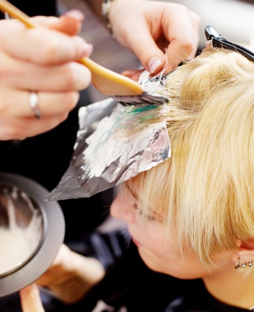 hairdresser applying color at womans hair